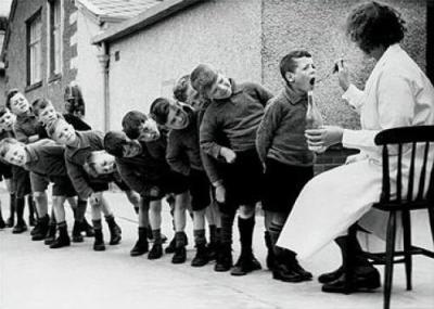 Una foto antica di una fila di bambini che prende olio di fegato di merluzzo da una infermiera